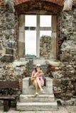 Junge touristische kaukasische Frau, die mit altem Fenster, Visegr aufwirft Stockbild