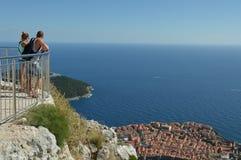 Junge touristische Paare, welche die Ansicht über alte Stadt von Dubrovnik genießen Stockbilder