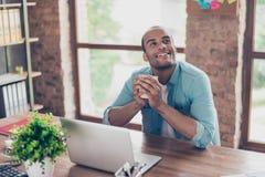 Junge träumende amerikanische Arbeitskraft des Mulatten denkt vor Laptop am Arbeitsplatz Er ist glücklich und lächelt, hinter ihm stockfotografie
