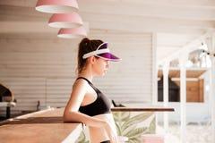 Junge tragen die Frau zur Schau, die nach Training am Strandcafé stillsteht Lizenzfreies Stockfoto