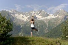 Junge tragen die Frau zur Schau, die Yoga im Sommer auf dem Hintergrund von schneebedeckten Bergen tut stockfotografie