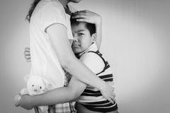 Junge traurig beim Umarmen der Mutter Stockfoto