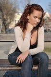 Junge traurige Frau, die auf Bank stationiert Lizenzfreie Stockfotografie