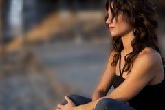 Junge traurige Frau, die durch sitzt Lizenzfreie Stockfotografie