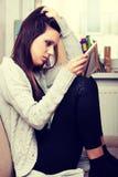 Junge traurige Frau, die im Kinderraum sitzt lizenzfreie stockfotografie
