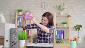 Junge traurige Frau, die moneybox langsames MO rüttelt stock footage