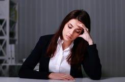 Junge traurige Geschäftsfrau, die am Tisch auf ihrem Arbeitsplatz sitzt Lizenzfreies Stockfoto