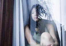 Junge traurige und deprimierte asiatische Chinesin, die durch die leidende Schmerz und Krise des Fensterglases in Traurigkeit con Stockbild