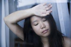 Junge traurige und deprimierte asiatische Chinesin, die durch die leidende Schmerz und Krise des Fensterglases in Traurigkeit con Stockfotografie