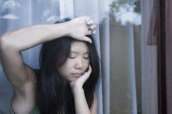 Junge traurige und deprimierte asiatische Chinesin, die durch die leidende Schmerz und Krise des Fensterglases in Traurigkeit con Lizenzfreie Stockfotos