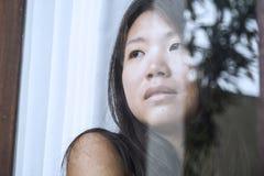 Junge traurige und deprimierte asiatische Chinesin, die durch die leidende Schmerz und Krise des Fensterglases in Traurigkeit con Lizenzfreie Stockbilder