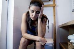Junge traurige und deprimierte bulimische Frau, die krankem Sitzen in Toilette WC schaut hoffnungslos und krank glaubt Stockfotos