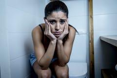 Junge traurige und deprimierte bulimische Frau, die krankem Sitzen in Toilette WC schaut hoffnungslos und krank glaubt Stockbilder