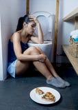 Junge traurige und deprimierte bulimische Frau, die krankes schuldiges glaubt, nachdem Pizza in WC-Toilette erbrochen worden ist Stockbilder