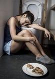 Junge traurige und deprimierte bulimische Frau, die krankes schuldiges glaubt, nachdem Pizza in WC-Toilette erbrochen worden ist Lizenzfreie Stockfotografie