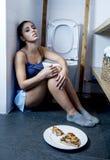 Junge traurige und deprimierte bulimische Frau, die krankes schuldiges glaubt, nachdem Pizza in WC-Toilette erbrochen worden ist Lizenzfreies Stockbild
