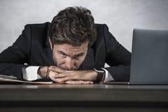 Junge traurige und deprimierte Geschäftsmannfunktion überwältigt und frustriert auf Laptop-Computer Schreibtischgefühlsumkippen u lizenzfreies stockbild