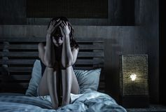 Junge traurige und deprimierte lateinische Frau, die auf durchdachtem des Betts sitzt Lizenzfreies Stockfoto