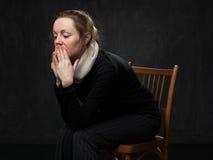 Junge traurige verwirrte Frau, die auf dem Stuhl sitzt Stockbilder