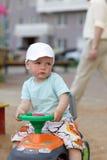 Junge treibt Spielzeug ATV an Stockbild