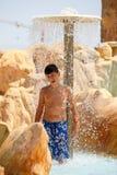Junge in tunesischem aquapark Erholungsort unter Dusche Lizenzfreies Stockfoto
