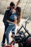 Junge umarmende und bei der Stellung des nahen Motorrads küssende Paare stockfotos