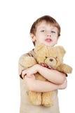 Junge umarmt Tragenspielzeug und sagt etwas. Stockfotos