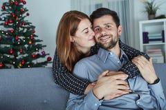 Junge Umarmung des glücklichen Paars auf Sofa stockbild