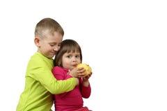 Junge umfasst kleines Mädchen mit Apfel in den Händen Lizenzfreie Stockfotografie