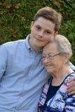 Junge umfasst liebevoll seine Großgroßmutter Stockbilder