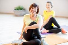 Junge und ältere Frauen, die Yoga tun lizenzfreie stockfotografie