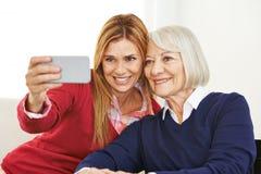 Junge und alte Frau, die zusammen selfie nimmt Lizenzfreies Stockfoto