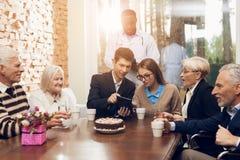 Junge und alte Leute sitzen zusammen am Tisch im Raum eines Pflegeheims Lizenzfreies Stockbild