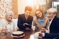 Junge und alte Leute sitzen zusammen am Tisch im Raum eines Pflegeheims Lizenzfreie Stockfotografie