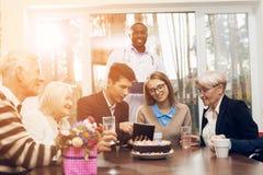 Junge und alte Leute sitzen zusammen am Tisch im Raum eines Pflegeheims Stockbilder