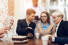 Junge und alte Leute sitzen zusammen am Tisch im Raum eines Pflegeheims Lizenzfreie Stockfotos