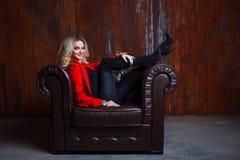 Junge und attraktive blonde Frau in der roten Jacke sitzt im Ledersessel, Füße auf der Armlehne Lizenzfreies Stockbild