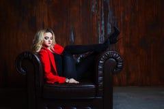Junge und attraktive blonde Frau in der roten Jacke sitzt im Ledersessel, Füße auf der Armlehne Stockfoto
