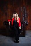 Junge und attraktive blonde Frau in der roten Jacke sitzt im Ledersessel, rostige Wand des Hintergrundschmutzes Lizenzfreie Stockfotos