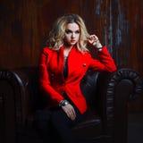 Junge und attraktive blonde Frau in der roten Jacke sitzt im Ledersessel, rostige Wand des Hintergrundschmutzes Stockfotografie