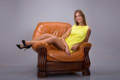 Junge und attraktive blonde Frau im gelben Kleid sitzt im Ledersessel, Füße auf der Armlehne Lizenzfreie Stockbilder