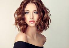 Junge und attraktive braune behaarte Frau mit moderner, modischer und eleganter Frisur Stockfotografie
