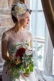 Junge und attraktive Braut, die am Fenster sitzt stockbild