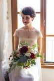 Junge und attraktive Braut, die am Fenster sitzt stockfoto