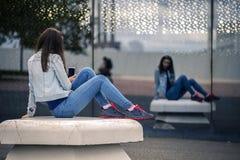 Junge und attraktive Frau sitzt auf der Bank im Industriepark Lizenzfreies Stockbild