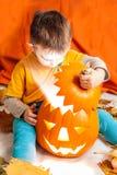 Junge und Beleuchten von Halloween-Kürbis Stockfotografie