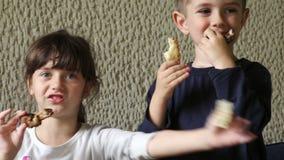 Junge und ein Mädchen, das Hühnerflügel isst stock video