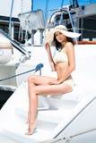 Junge und geeignete Brunettefrau, die in einem Badeanzug auf einem Boot sich entspannt Lizenzfreies Stockfoto