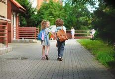 Junge und gerlie gehen zur Schule, die Händen angeschlossen wird Stockbilder