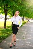 Junge und glückliche Geschäftsfrau, die in Stadtgrünpark geht Stockfotos